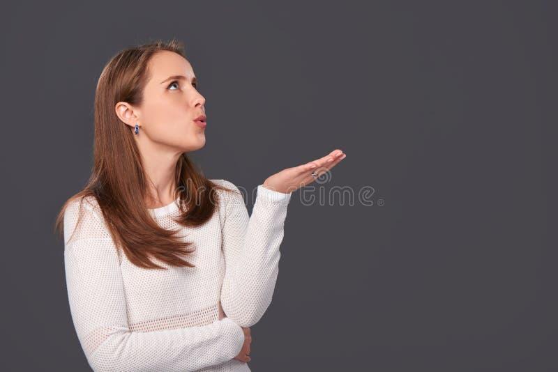 Profilståenden av en kvinna som blåser på, gömma i handflatan royaltyfri foto