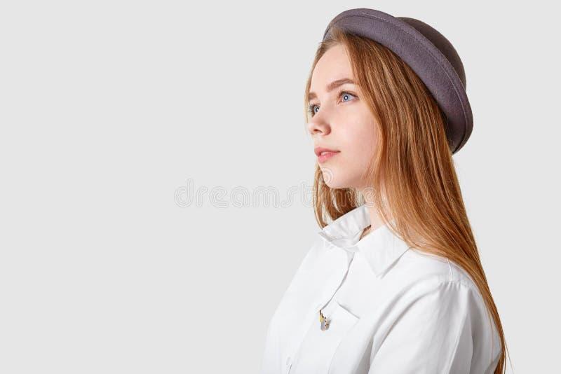 Profilu strzał rozważna kobieta jest ubranym kapeluszową i elegancką koszula, skupiającą się w odległość, nad białym tłem z bezpł obrazy stock
