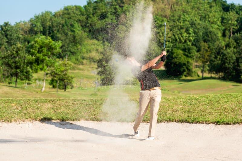 Profissão asiática Golfer saindo de uma armadilha de areia O campo de golfe está na areia Hobby em férias e férias no golfe clube fotografia de stock royalty free