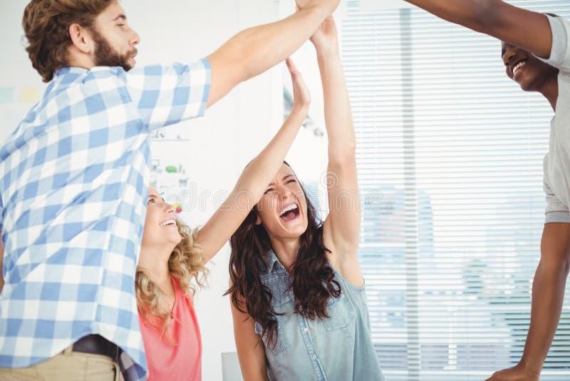 Profissionais de sorriso do negócio que dão a elevação cinco na mesa fotografia de stock royalty free