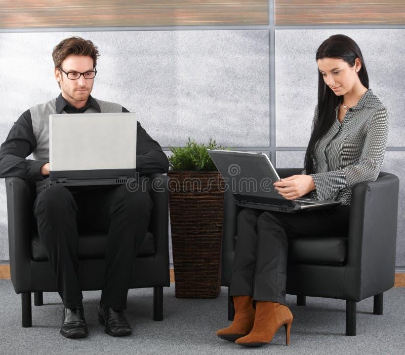 Profissionais novos na entrada do escritório com portátil fotos de stock royalty free