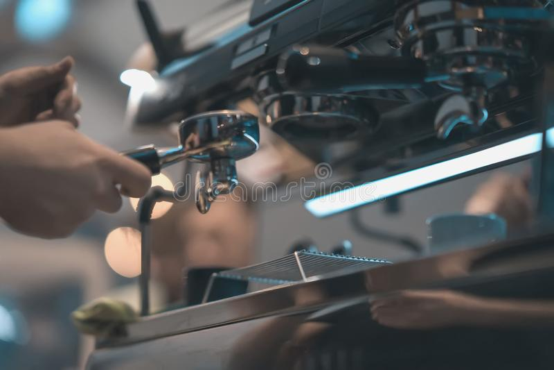 Profissional do close-up que mói o café recentemente roasted na máquina de café Barista que prepara o café na barra Conceito de foto de stock