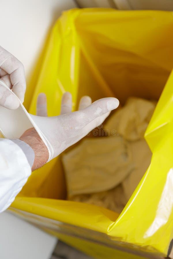 Profissional dos cuidados médicos que joga afastado luvas descartáveis do látex no lixo fotografia de stock royalty free