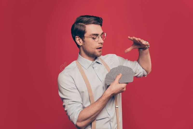 Profissional, mágico astuto, ilusionista, jogador no equipamento ocasional, vidros, guardando plataforma de cartões ajustada, faz imagem de stock