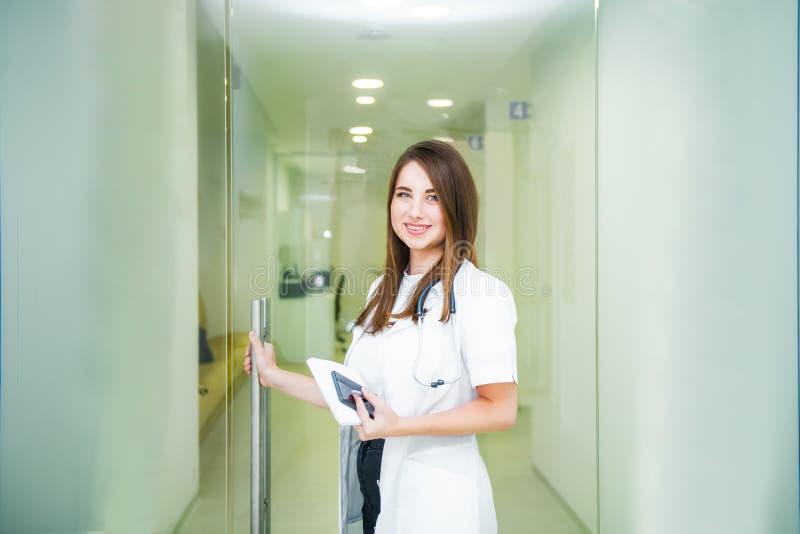 Profissional médico fêmea novo de sorriso, doutor com o estetoscópio e o telefone esperto que olham a câmera e que abrem a porta  imagens de stock royalty free