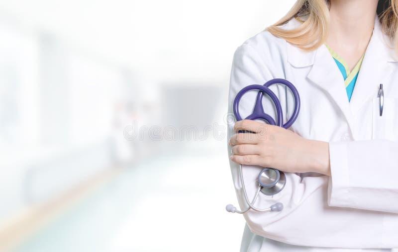 Profissional médico fêmea que guarda um estetoscópio roxo nela fotografia de stock