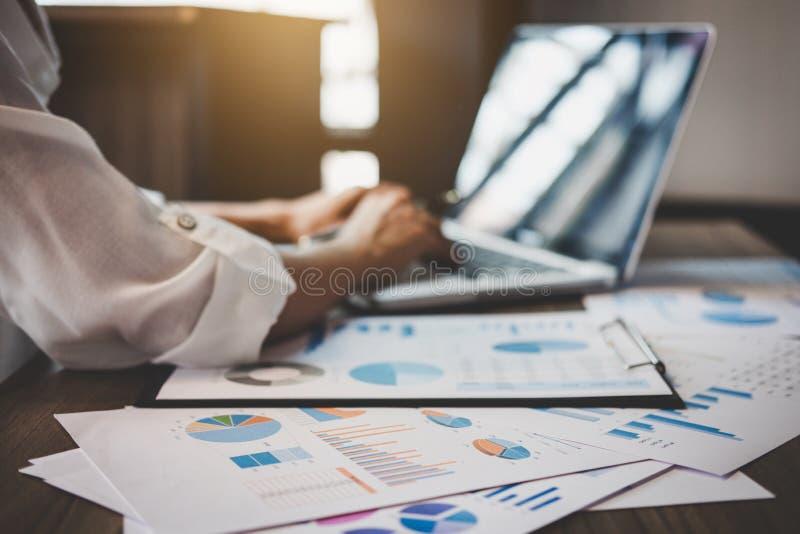 Profissional no trabalho, no funcionamento da mulher de negócio e na análise no portátil com gráfico financeiro dos dados do docu imagem de stock