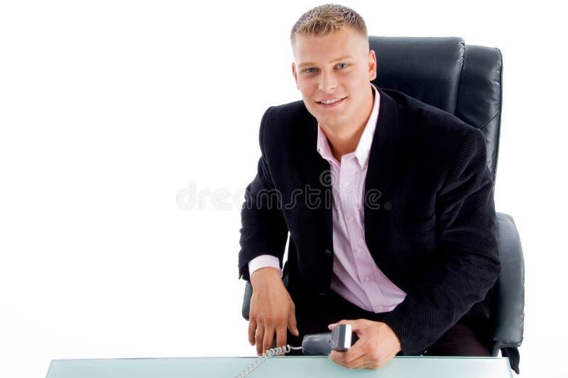 Profissional novo de sorriso na mesa de escritório fotografia de stock royalty free