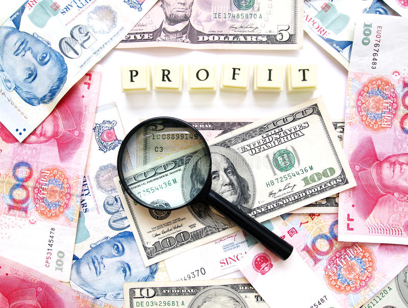 Profit concept. A photograph of some different currency money in dollar bills, taken as a background with the word profit spelt out in blocks, and a magnifying royalty free stock photography