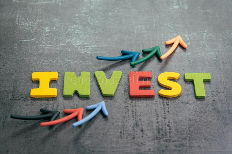 Profit or growth from investment concept, arrows pointing up as chart with colorful letters building the word INVEST on loft stock photography