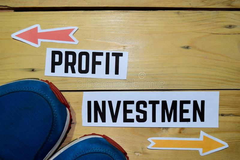 Profit or Investment opposite direction signs with sneakers on wooden vintage background. Business and education concepts royalty free stock photography