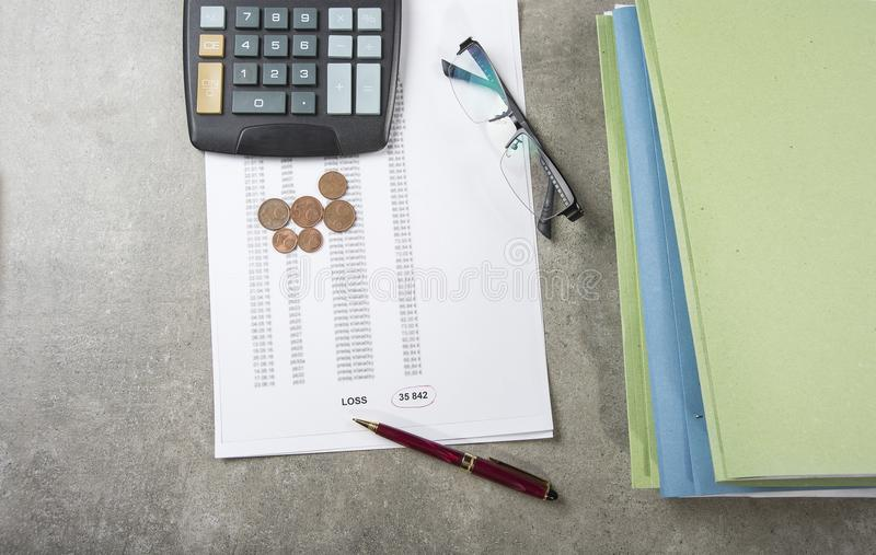 Profit and loss concept image of a pen, calculator and coins on financial documents.  stock images