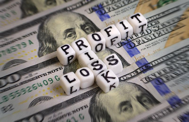 Profit or Loss, or Risk concept with letter cubes on a dollar bank notes. royalty free stock photography