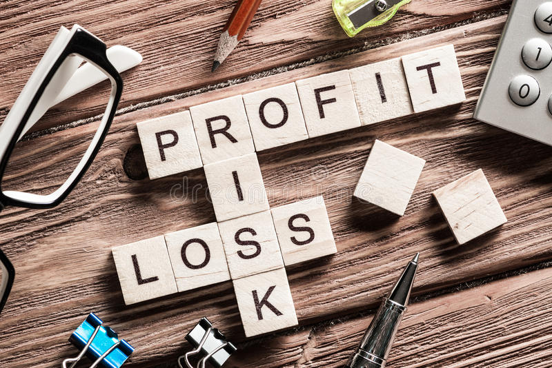 Profit loss and risk words on workplace collected of wooden cubes. Concept of risk in business presented by crossword stock photo