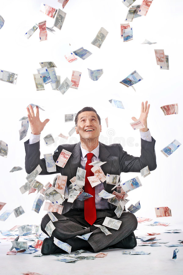 Profit-maximizing. Papermoney flys down on a sitting businessman royalty free stock image