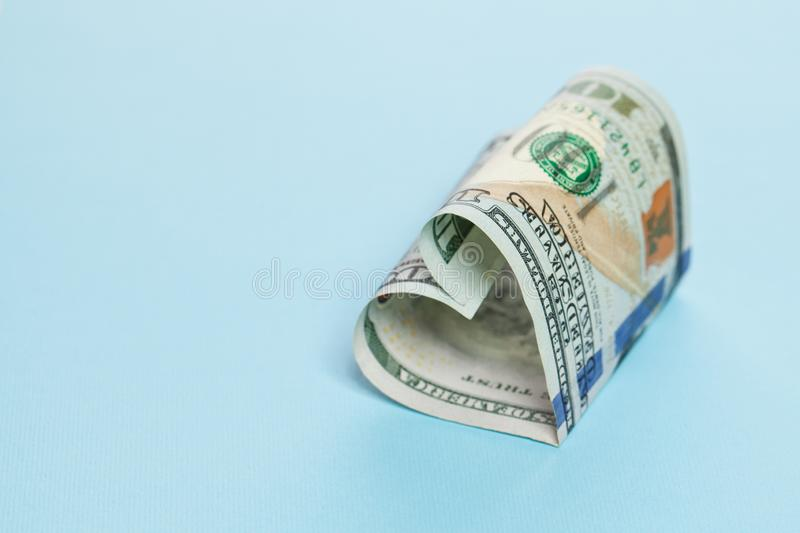 Profit and money gift concept. 100 note US dollars cash heart shape on blue background with copy space.  royalty free stock photo
