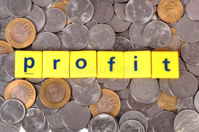 Profit. Spelled on coin background stock images