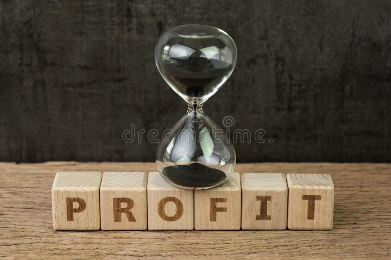 Profit, time for company or investment that get revenue more than expense, hourglass or sandglass on wooden cube block with royalty free stock photography