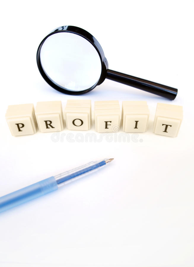 Profit word. A concept photograph of the word profit spelt out in blocks, taken with a magnifying glass and a blue pen, on clean white background with copy space royalty free stock images