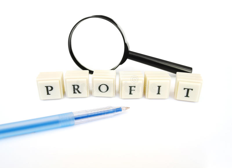 Profit word. A concept image of the word profit spelt out in blocks. Taken with magnifying glass and blue pen, on white background with copy space, nobdoy in stock photography