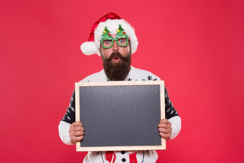 Profitable offer here. Rental services. Winter price drop. Bearded hipster Santa claus. Joyful man show blackboard copy royalty free stock photo