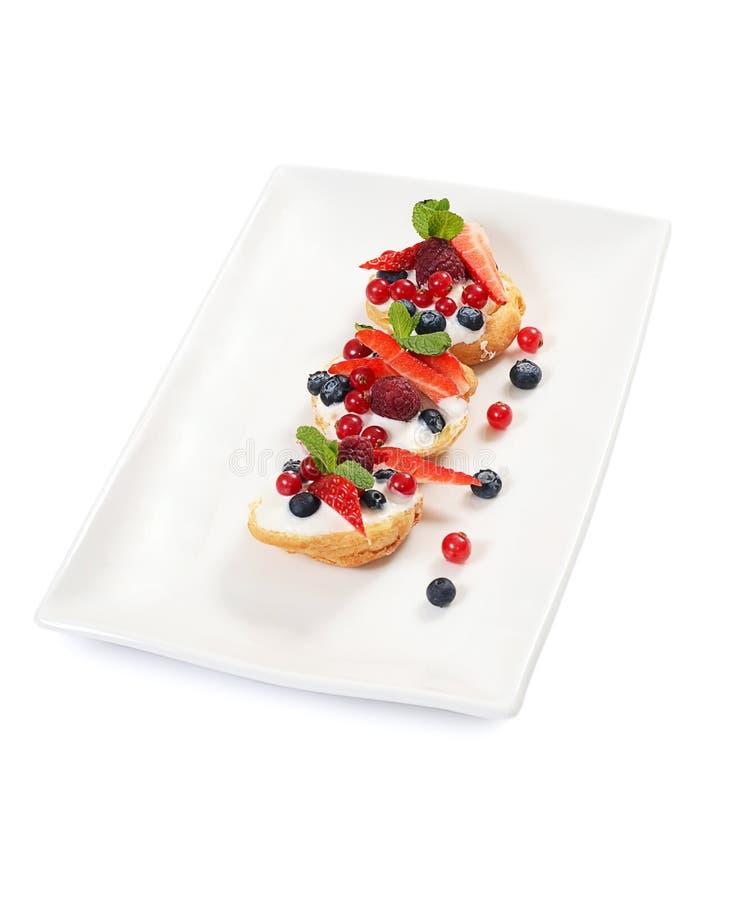Profiteroles с ягодами смородиной, клубниками и голубиками стоковая фотография