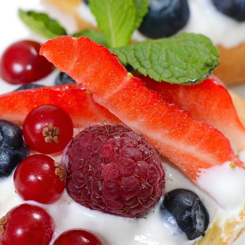 Profiteroles с ягодами смородиной, клубниками и голубиками стоковое изображение