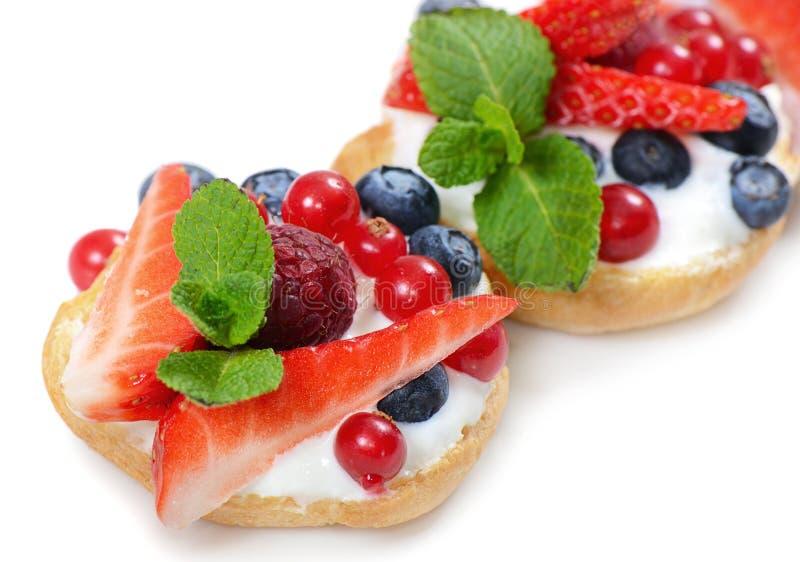 Profiteroles с ягодами смородиной, клубниками стоковое изображение
