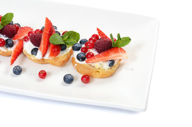 Profiteroles с ягодами смородиной, клубниками стоковая фотография rf