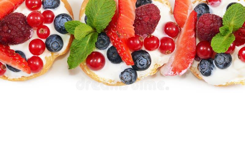Profiteroles с ягодами смородиной, клубниками стоковое фото