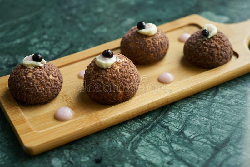 Profiteroles brancos do chocolate com violeta do pêssego Bolo fotografia de stock
