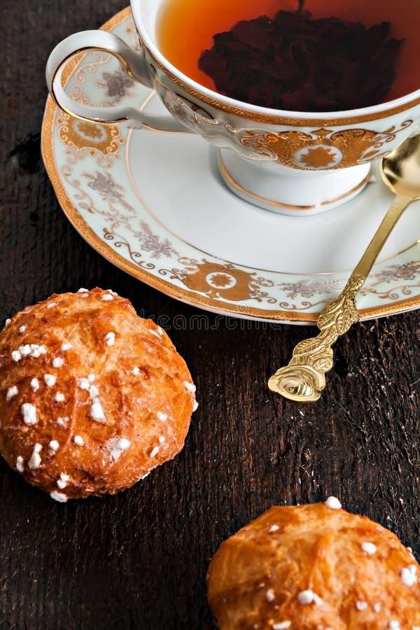 Profiteroles cobriu com açúcar e copo do vintage com chá em um dar foto de stock royalty free