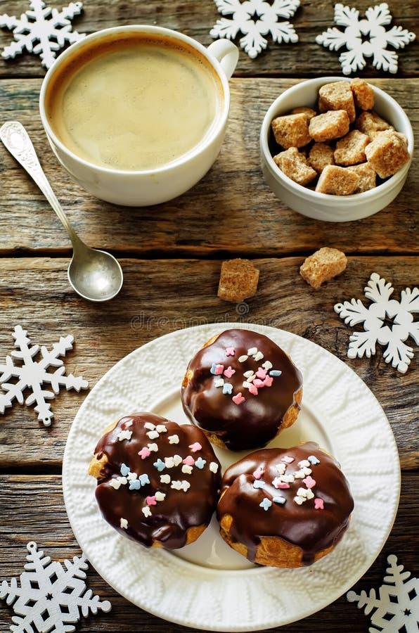 Profiteroles com crosta de gelo do chocolate e pó e café coloridos imagens de stock