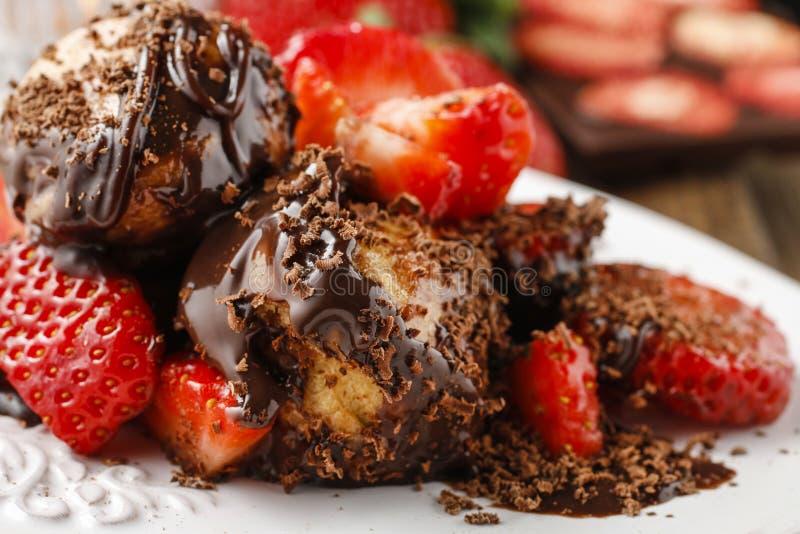 Profiteroles com morangos e molho de chocolate imagens de stock royalty free