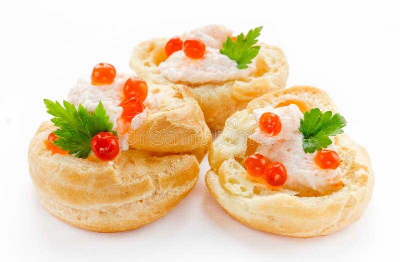 Profiteroles com musse de peixes ou pasta e fim vermelho do caviar está acima imagens de stock