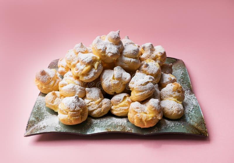 Profiteroles de las tortas asperjados con el azúcar en polvo en un fondo rosado Eclairs hechos en casa imagenes de archivo