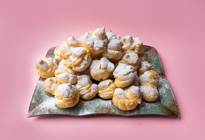 Profiteroles de las tortas asperjados con el azúcar en polvo en un fondo rosado Eclairs hechos en casa foto de archivo libre de regalías
