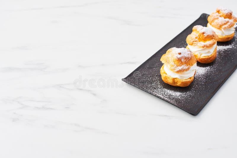 Profiteroles deliciosos com creme e açúcar pulverizado em uma placa imagens de stock royalty free