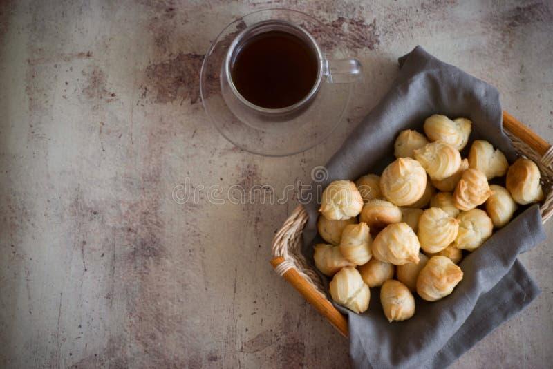 Profiteroles do ar em um guardanapo na cesta Um copo do café quente em um fundo bonito fotos de stock