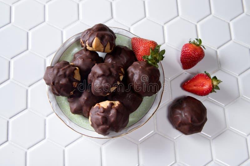 Profiteroles eclairs med choklad och jordgubbar royaltyfria foton