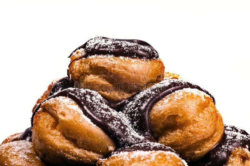 Profiteroles en un fondo belga rico del blanco del primer del chocolate del montón fotos de archivo libres de regalías