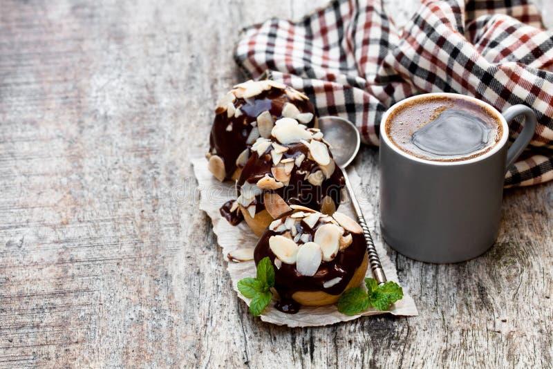 Profiteroles hechos en casa con las almendras y la taza de café en de madera foto de archivo libre de regalías
