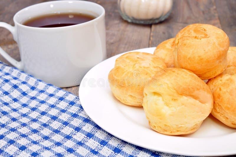 Profiteroles und eine Tasse Tee stockfotos