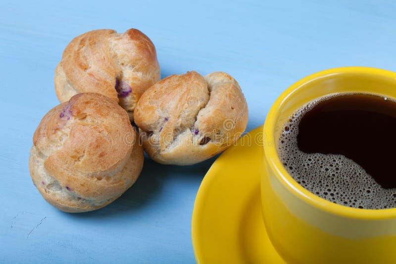 Profiteroles y taza de café hechos en casa frescos en la tabla de madera azul fotos de archivo libres de regalías