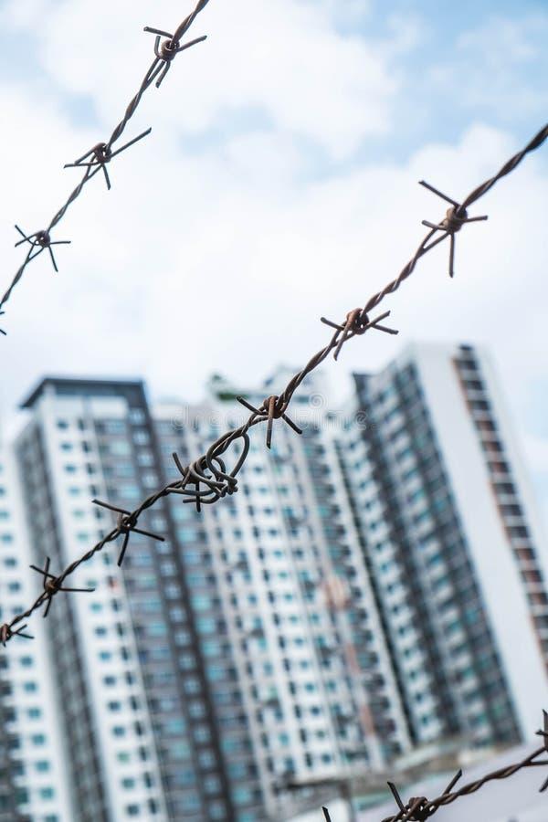 Profondeur du champ, vieux fil d'acier dénudé contre le ciel bleu avec les bâtiments modernes brouillés photographie stock libre de droits
