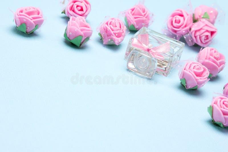 Profumi la bottiglia con le piccoli rose ed arco rosa immagini stock