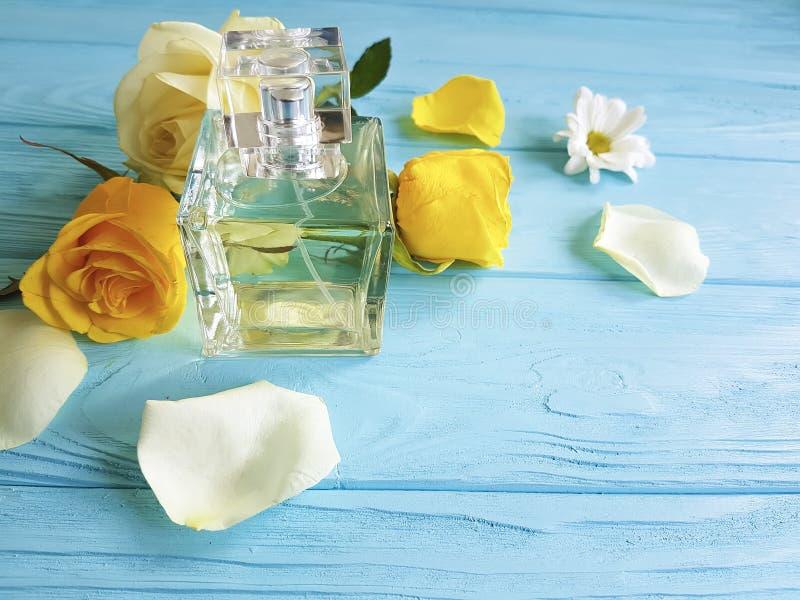 Profumi la bottiglia dell'aroma dell'essenza brillante con la decorazione delle rose gialle su un fondo di legno fotografie stock libere da diritti