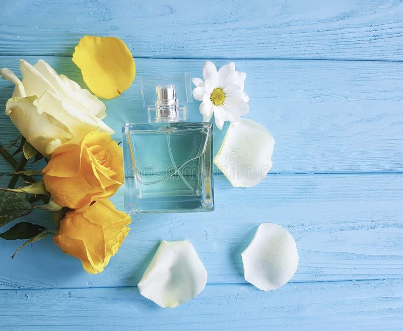 Profumi la bottiglia dell'aroma dell'essenza con la decorazione delle rose gialle su un fondo di legno fotografia stock libera da diritti