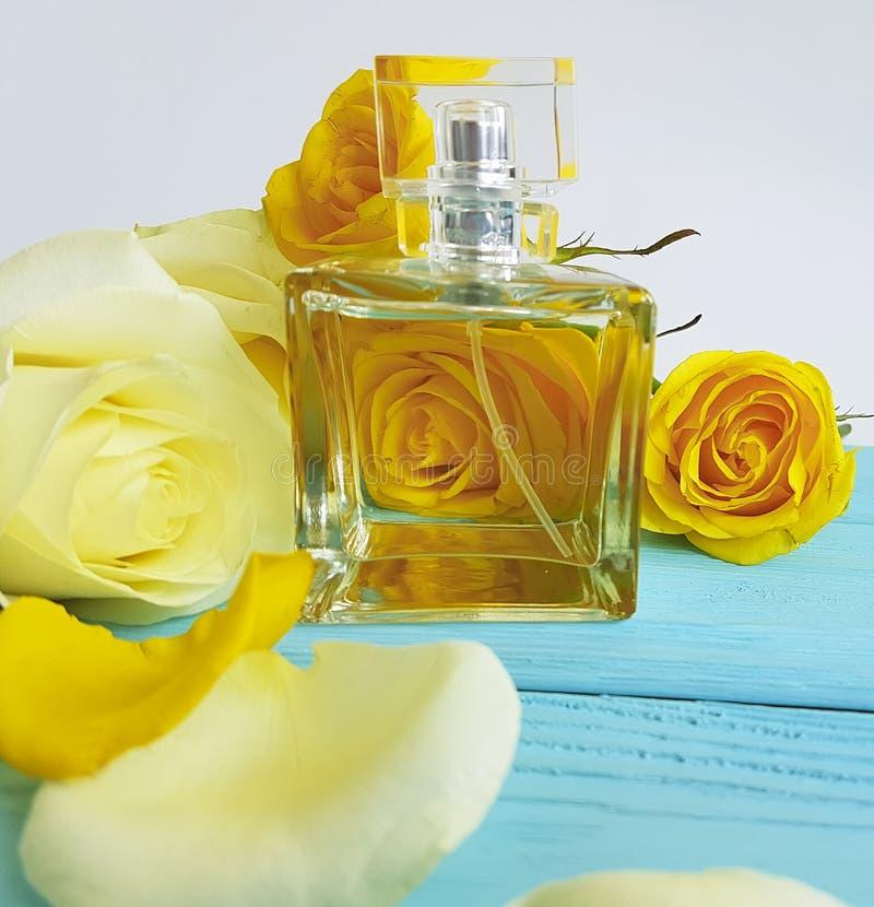 Profumi la bottiglia dell'aroma dell'essenza con le rose gialle su un fondo di legno fotografia stock libera da diritti