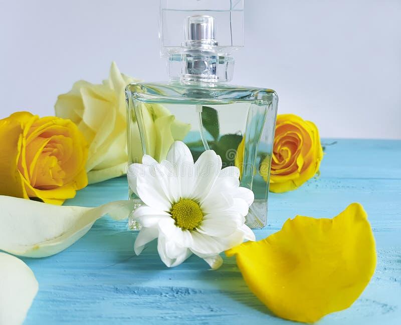 Profumi la bottiglia dell'essenza con le rose gialle su un fondo di legno fotografia stock libera da diritti